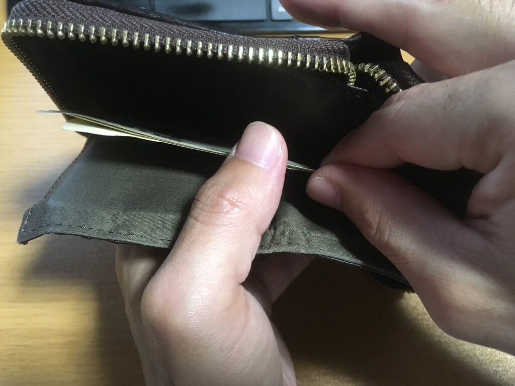 元々使っていたポーター(PORTER)の二つ折り財布からお札を取り出す