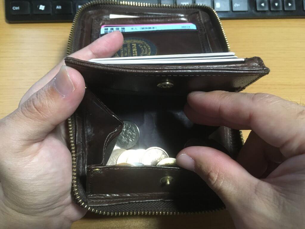 元々使っていたポーター(PORTER)の二つ折り財布から小銭を取り出す
