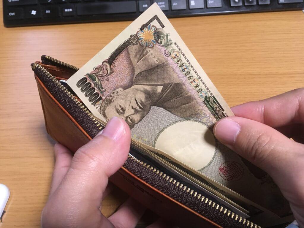 キャサリンハムネットロンドン(KATHARINE HAMNETT LONDON)L字ファスナー長財布からお札を取り出す